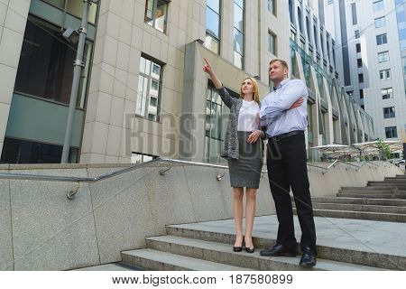 full height portrait of Businessman and businesswoman showing to the distance outdoor.