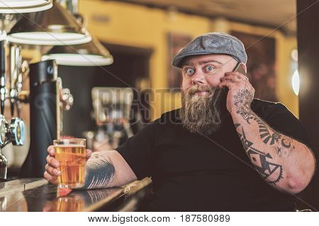 Shocking news. Portrait of bearded man talking on smartphone while expressing astonishment. He looking at camera while holding glass of beer