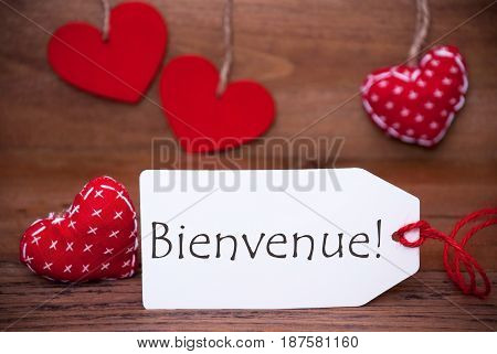 Label With French Text Bienvenue Means Welcome. White Label With Red Textile Hearts. Retro Brown Wooden Background.