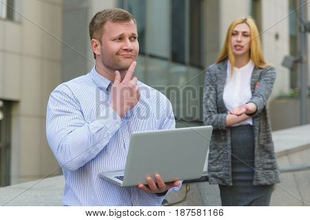 Clever businessman with laptop ahead of business lady who talking to him outdoor.