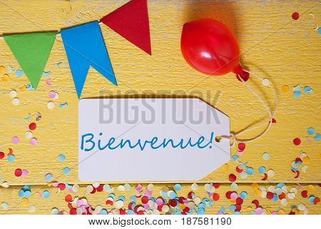 White Label With French Text Bienvenue Means Welcome. Party Decoration Like Streamer, Confetti And Balloon. Flat Lay Or Top View. Yellow Wooden Background