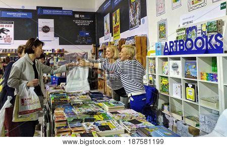 KIEV - UKRAINE - MAY 2017:  Art and book exhibition in Arsenal museum in Kiev. Vendors of books give buyers bought books. Everyone is smiling