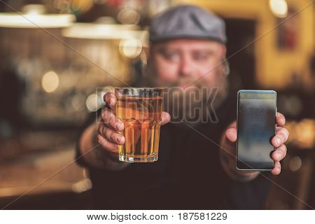 Make choice. Cheerful obese man showing black screen of smartphone and glass of beer on camera. Focus on mobile phone and mug