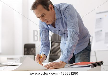 Little changes. Concentrated senior professional engineeer standing near table and drawing blueprint while working in the office