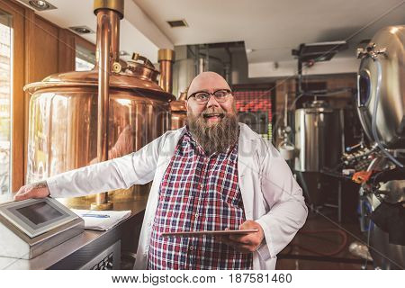 Love my job. Portrait of cheerful bearded man posing in brewery while making beer. He looking at camera with joy