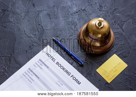 hotel reception desk with booking form on dark background