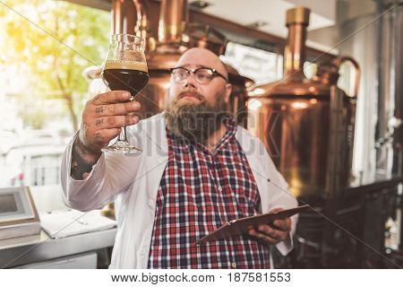 Perfect beverage. Concentrated smart delighted man working as brewer. He examining glass of beer carefully. Focus on dark ale
