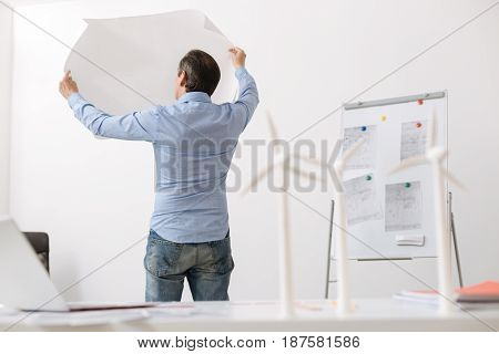 Involved in important project. Back view of professional engineer standing in the office with blueprint in hands while models of wind turbines standing in the background