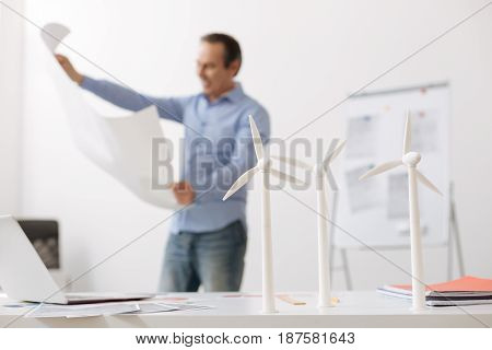 Eco engineering. Positive professional engineer standing with blueprint in hands in the office while models of wind turbines standing on the table