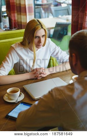 Business meeting in a cafe. Angry woman looks at man. Poor results and failure concept.