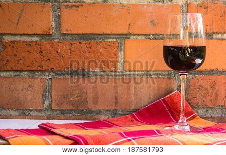 A glass of red wine on a brick wall background