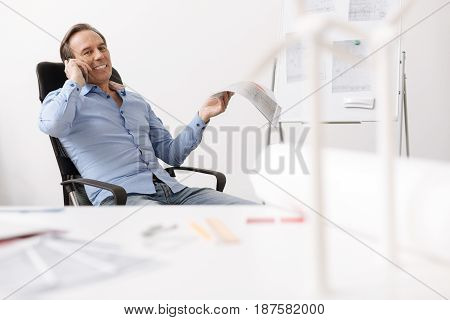 Pleasure to talk with you. Positive senior engineer sitting at the table and talking on cell phone while working in the office