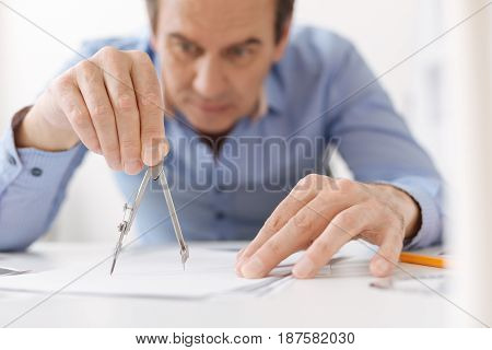Pay attention to details. Professional skillful architect holding compasses and drawing a scheme while working on the project