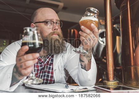 Comparing tastes. Serious worker holding two glasses of dark and light beer while checking the quality of beverages. Focus on brewer