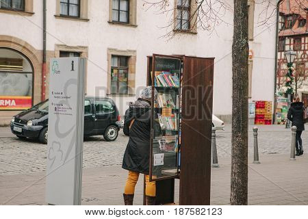 Furth, Germany, December 28, 2016: A woman chooses a book. Street public library. Education in Germany. Lifestyle. Everyday life in Europe