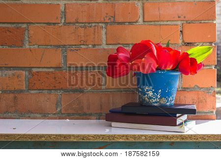A stack of books and a pot of spring flowers against a brick wall background