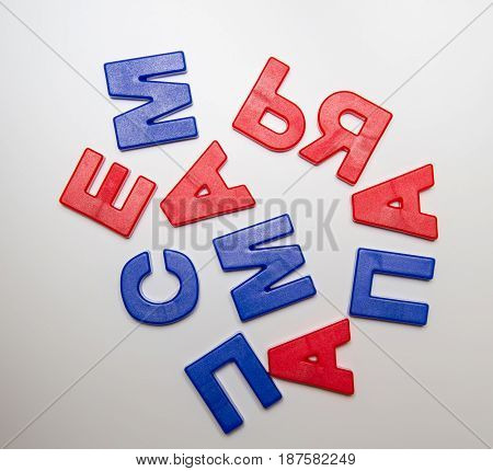 Russian language. Plastic letters with a magnet are arranged in a chaotic order but from these words are easily read: family I mom dad. Cyrillic.