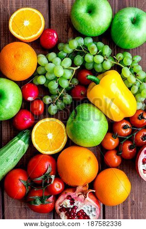 Organic fruits and vegetables for healthy dinner on wooden background top view