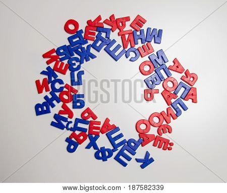 Russian language. Plastic letters with a magnet in a chaotic order are arranged in the form of a circle. In the center of this circle is an empty space. Cyrillic.