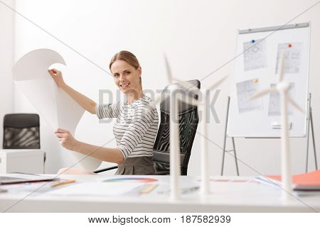 Lets find new ideas. Positive smiling professional woman sitting in the office and holding blueprint while working on the project of building eco wind turbines