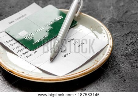 credit card for paying, plate, pen and check on cafe gray stone desk background