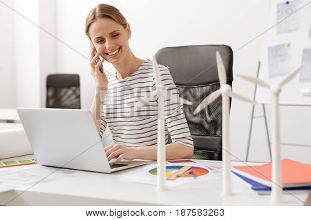 Best way to communicate. Positive attractive professional woman sitting at the table and talking on smart phone while designing wind turbines
