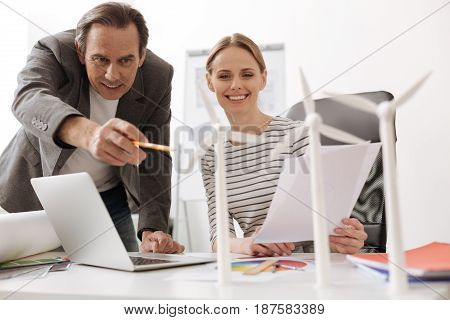 Brainstorm your ideas. Cheerful professional colleagues looking at the wind turbines models while working together in the office