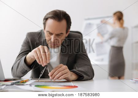Precise measurements. Concentrated serious engineer sitting at the table and drawing while working in the office with his colleague