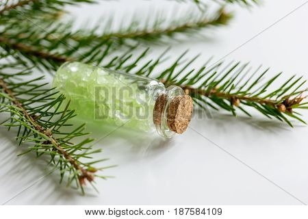 natural fir branches and spruce bath salt on white table background