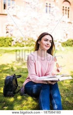 Young Beautiful Woman Student In Summer Park Reading A Book On The Grass