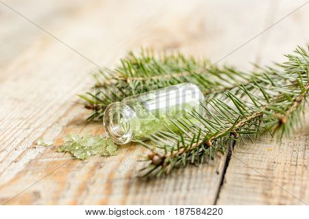 cosmetic spruce salt in bottles with fur branches for aromatherapy on wooden table background