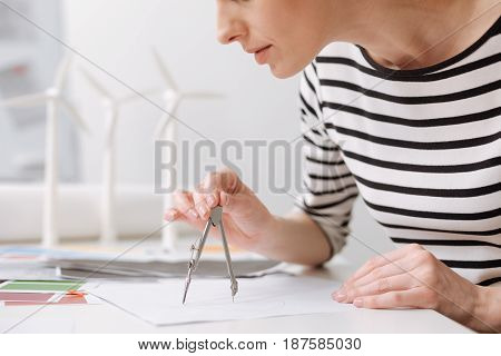 Accurate work. Concentrated professional female engineer sitting at the table and drawing with compasses while working on the project of wind turbines