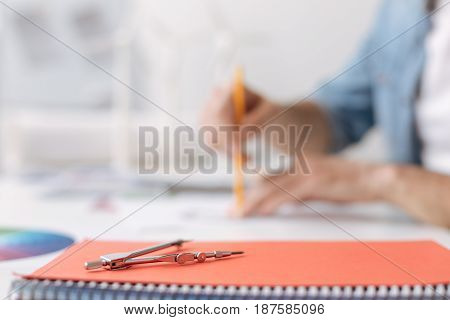 Important tool. Selective focus of a protractor lying on the table while a professional engineer sitting in the background