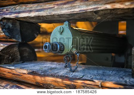 The barrel of a machine gun sticking out of an embrasure with a shallow depth of field
