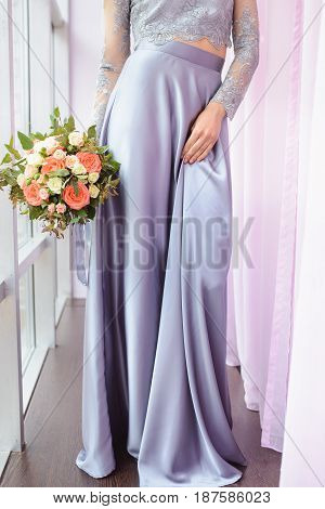 Beautiful woman in a plum dress holding a bouquet of roses, closeup detail shoot, focus on flowers.