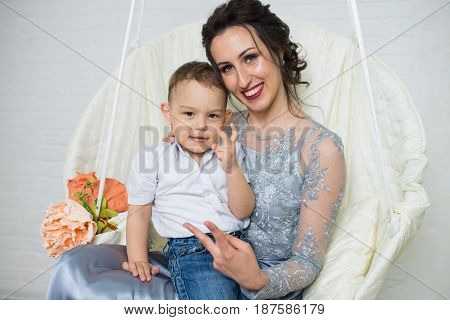 Happy family of young beautiful mother in plum dress and little positivity son, gesturing victory by fingers