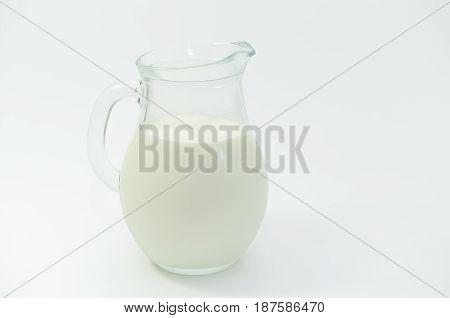 Fresh cow milk in a jar on a light background