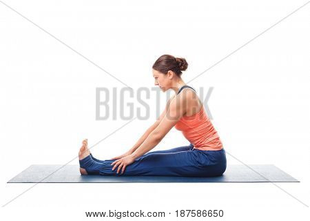 Sporty fit woman doing Ashtanga Vinyasa yoga back bending asana Paschimottanasana - seated forward bend beginner easy variation isolated on white