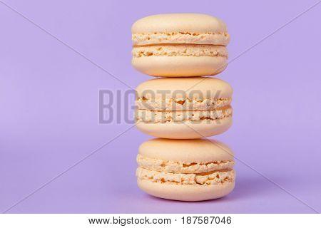 Image of three sweet orange macaroons on purple table background.