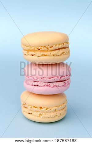 Picture of three sweet colorful macaroons on blue table background.