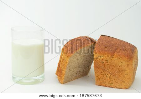 Milk in a glass on a light background with fresh crusted bread