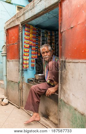 Jodhpur, India - March 7, 2016: Unidentified indian seller sit in the window of his street shop colored in national flag colors in Jodhpur, India