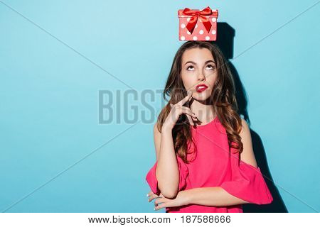 Confused girl in dress with gift box on her head looking up isolated over blue background