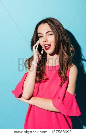 Portrait of a pretty brunette girl in dress winking while talking on mobile phone isolated over blue background