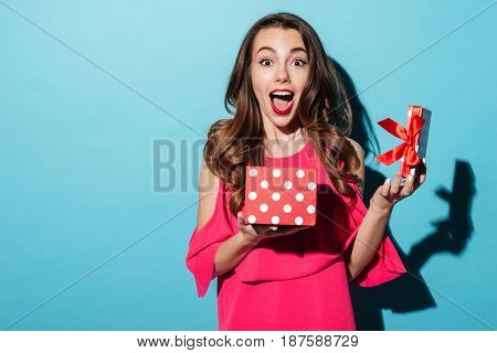 Portrait of an excited cute girl in dress holding opened present box isolated over blue background