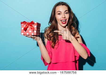 Portrait of an excited smiling girl in dress pointing finger at a gift box isolated over blue background