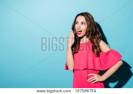 Portrait an excited pretty girl trying to cover her mouth with hand isolated over blue background