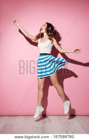 Full length portrait of a casual pretty girl in dress jumping over pink background