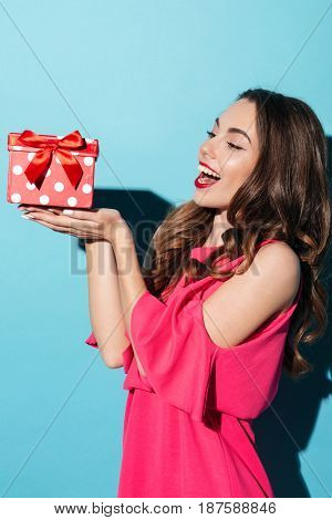 Side view portrait of a smiling pretty girl in dress holding gift box on her palms isolated over blue background