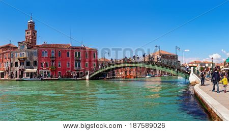MURANO, ITALY - APRIL 20, 2016: Panoramic view of old colorful houses and bridge over canal in Murano - island located in Venetian lagoon, popular tourist destination, famous for its glass making.